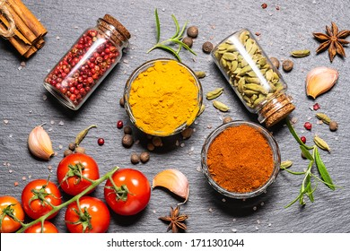 Set of spices and vegetables on black stone background top view.
