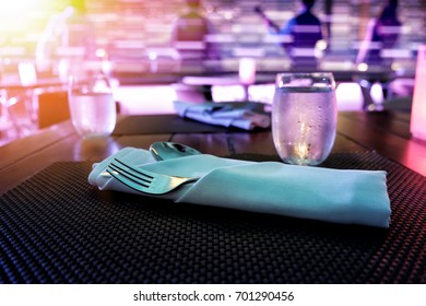 set of spoon and fork on a diner table with drinking water.