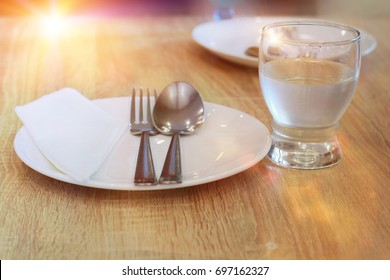set spoon and fork on dish for breakfast on table wooden in morning time