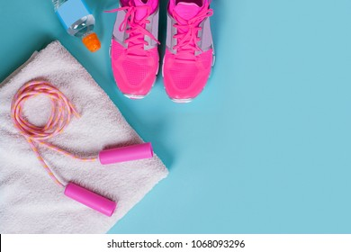 Set of Sporting Equipment - Pair Sport Shoes, a Skipping rope with a white Towel and a Bottle of cool Water on Blue Background. Concept Healthy lifestyle, energy Sport and diet. Sport equipment