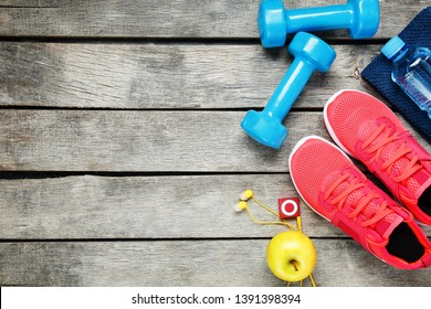 Set of sports accessories for fitness concept with exercise equipment on gray wooden background.