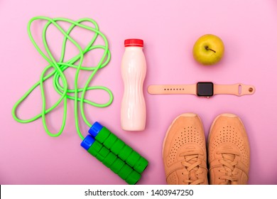 Set for sports activities and smart watch, apple and sneakers on pink background. Fitness and healthy life concept. Sport shoes, dumbbells and skipping rope on pink background. Top view for bloggers.