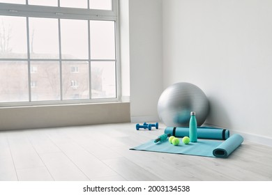 Set of sports equipment with fitness ball near light wall