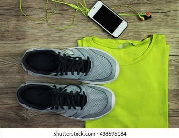Set for sports: shoes, t-shirt, mobile phone with headphones  close-up on a wooden background, top view