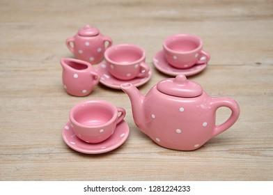A set of spotted pink porcelain tea set on a wooden background