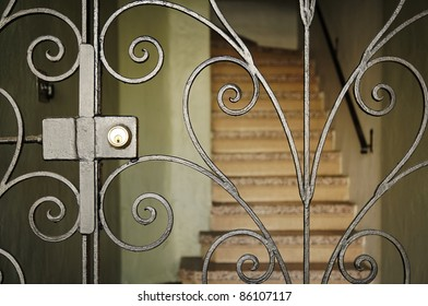 Set of stairs of a residence, blocked by an elegant metal gate. Vertical shot.
