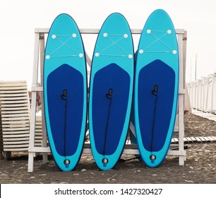 Set of stand-up paddleboard for SUP surfing in surf station on beach