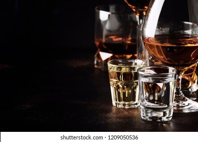 Set of strong alcoholic drinks in glasses and shot glass in assortent: vodka, rum, cognac, tequila, brandy and whiskey. Dark vintage background, selective focus