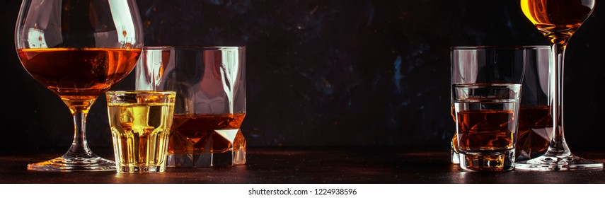 Set of strong alcoholic drinks in glasses and shot glass in assortent: vodka, rum, cognac, tequila, brandy and whiskey. Dark vintage background, banner, selective focus