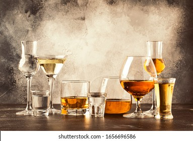 Set of strong alcoholic drinks in glasses in assortment: vodka, cognac, tequila, brandy and whiskey, grappa, liqueur, vermouth, tincture, rum. Gray bar counter background, copy space, toned