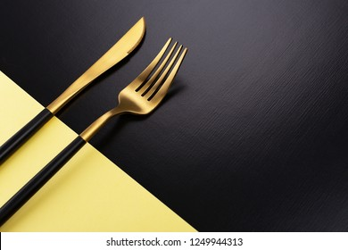 Set of stylish black and gold cutlery on color block background. Dark and moody vibes. Fashionable and luxury eating. Flat-lay, top view. Copy space for your text.