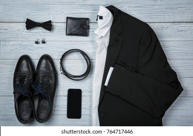 Set of stylish male clothes and accessories on wooden background