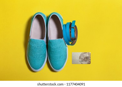 set of stylish women blue slip on shoes, credit card and a belt on the yellow surface. view from the top. spring summer hipster trend. free space for advertising text. mockup for instagram