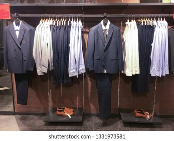 Set of suits with shirts, shoes, handbag in shop