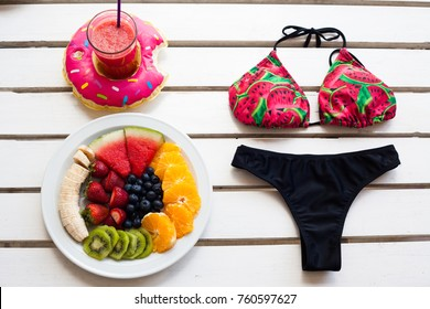 Set of summer. Fresh fruit plate, bikini and drink, top view from above.