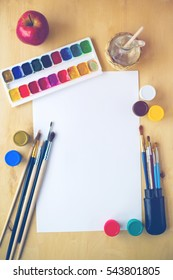 Set of supplies for drawing: watercolor brushes, color palette, gouache, color paper, decanter with water on wooden background. Art painting concept. Copyspace.