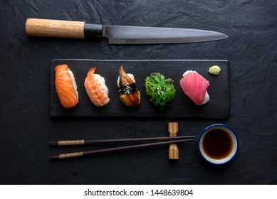 Set of sushi and knife on dark stone table. Top view with copy space