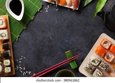 Set of sushi and maki roll and green tea over stone table. Top view with copy space