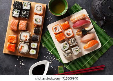 Set of sushi and maki roll and green tea on stone table. Top view