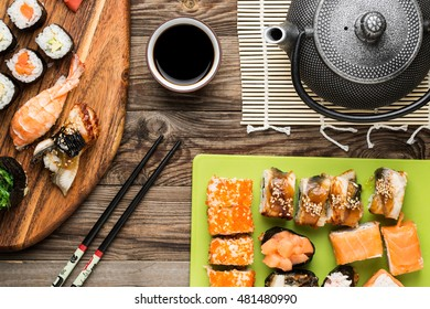 Set of sushi rolls, chopsticks, soy sauce and teapot, serving traditional Japanese food