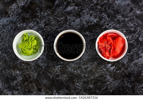 Set for sushi soy sauce ginger wasabi with chopstick on black stone background