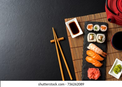 Set of sushi with wasabi, soy sauce and teapot on black stone background