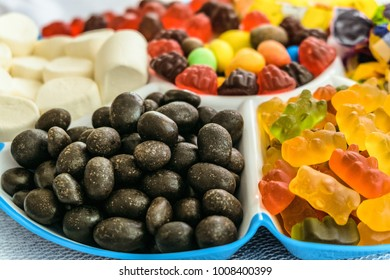 Set of sweet loose candies in a tray. Heaps of peanuts in chocolate-sugar glaze, marmalade bears and berries, marshmallows. Tasty grocery background with limited depth of field.