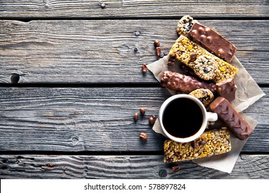 Set of sweets with a cup of coffee. Chocolate bars and granola on a wooden background with milk chocolates. Food, candy, snack