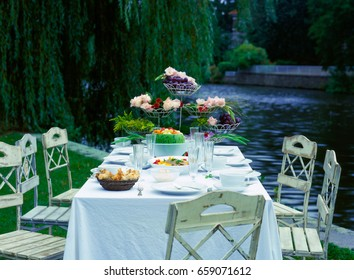 Set table and chairs outside in the grass by the water
