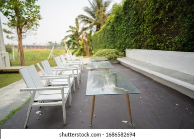 set of table and white chairs in the garden