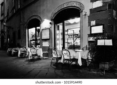 Set tables on patio of Italian restaurant in medieval alleyway of Lucca, Tuscany, Italy