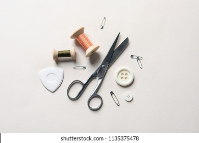 Set of tailoring accessories on light background, top view
