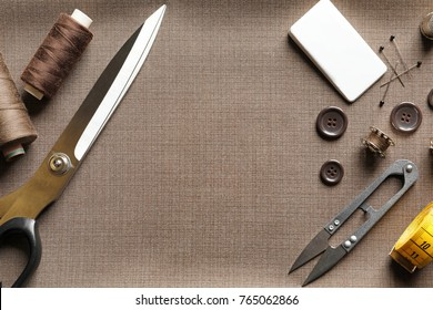 Set of tailoring tools and accessories on fabric, top view