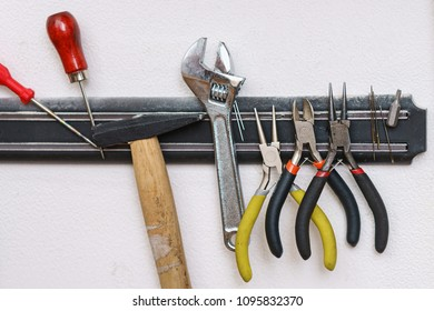 Set of tanner tools close-up. An awl, screwdriver, hammer, wrench, pliers and wire cutters hang on magnetic holder.