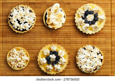 Set of tartlets with lemon curd, berry confiture and meringue top view