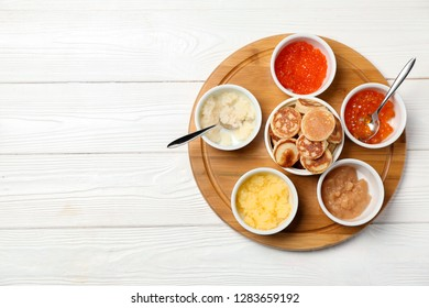 Set of tasty caviar with flapjacks on white wooden table