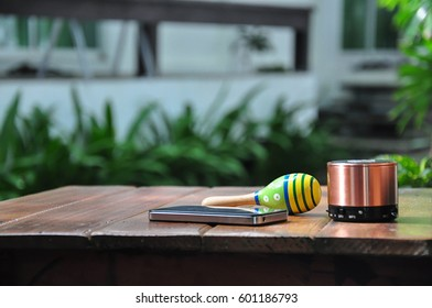 Set of technological and traditional music maker or instrument or gadget including Maracas or egg shaker, Smartphone and compact usb speaker on wooden table