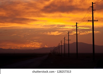 A set of telephone poles stretch into the distance along a highway in California at sunset.