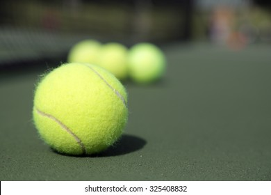 Set of tennis balls on a green tennis court