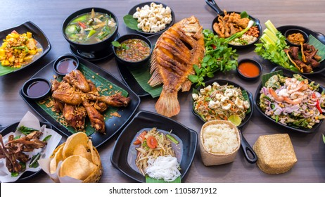 Set of Thai food - Papaya salad, Fried fish, Fried chicken,  Sea food spicy salad and Sticky rice