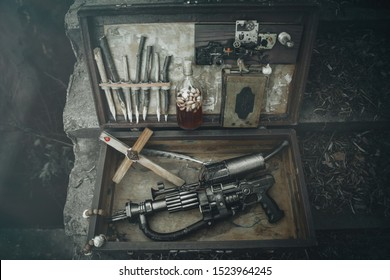 A set of things hunter evil spirits, demons, vampires in an old suitcase. An old book with spells, aspen stakes, tincture of garlic and Holy water, rosary, cross and gun. The view from the top