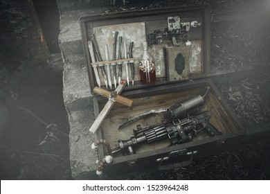 A set of things hunter evil spirits, demons, vampires in an old suitcase. An old book with spells, aspen stakes, tincture of garlic and Holy water, rosary, cross and gun. The view from the side