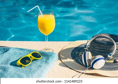 A set of things to relax by the pool on vacation - sunglasses, a hat, a glass of orange juice, headphones
