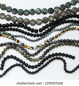 Set of threads different semiprecious gemstones beads in dark colors,jasper camouflage,black agate,labrador,jade,hematite,larvikit,lava and pyrite on the white background,top flat lay view.