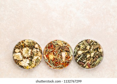 a set of three Chinese herb teas in round bowls against ceramic background with a copy space