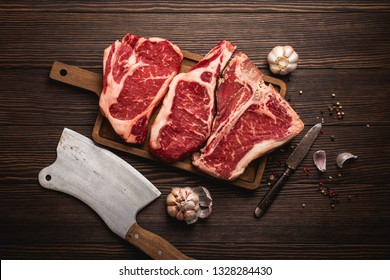 Set of three different types raw meat steaks: Ribeye, T-bone, Cowboy on cut board with knife and seasonings, wooden background. Aged steaks assortment, butchery/restaurant concept, top view, close up