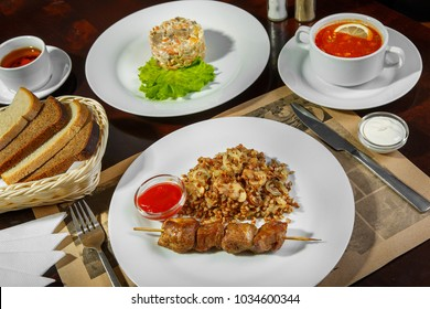 A set of three dishes for business lunch. Buckwheat porridge and barbecue from the meat, beef, hodgepodge with sour cream and lemon, governor's salad, bread, tea. Serving dishes in a restaurant, cafe