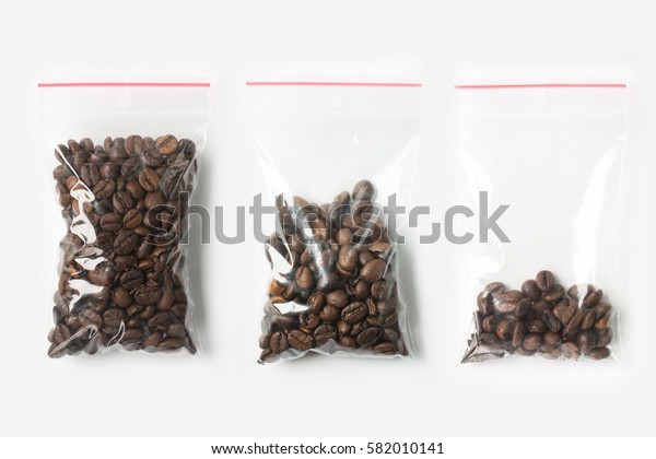 Set of three EMPTY, HALF AND FULL Plastic transparent zipper bag with coffee beans isolated on white. Vacuum package mockup with red clip. Concept.