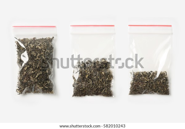 Set of three EMPTY, HALF AND FULL Plastic transparent zipper bag with dry green tea isolated on white. Vacuum package mockup with red clip. Concept