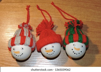 A set of three handmade snowmen heads made of table tennis plastic balls and bobble hats made of wool, Christmas baubles